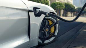 Weißer Porsche Taycan wird an einer Ladesäule aufgeladen